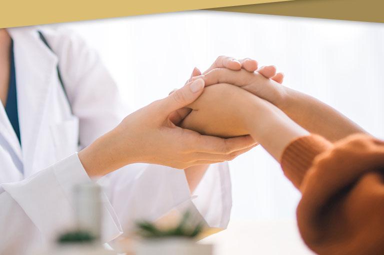 Lekarka trzymająca dłonie pacjentki